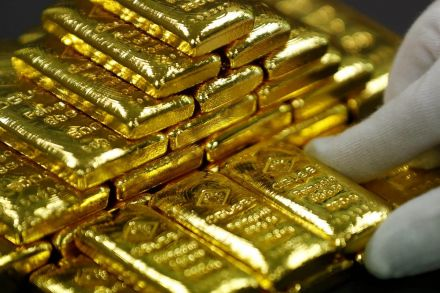 Gold edges down on firmer dollar, higher bond yields