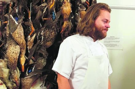 Chef_Magnus_Nilsson_in_front_of_the_'duck_wall'__where_game_birds_are_aged_for_up_to_two_weeks.jpg