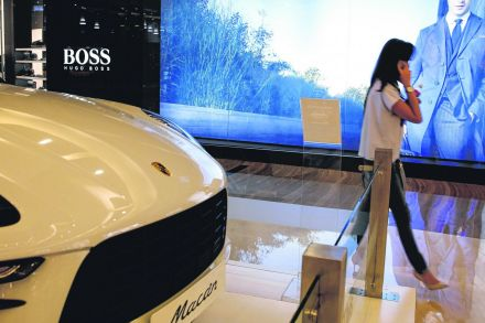 A shopper walks past a Porsche on display at a mall in Jakarta, Indonesia.