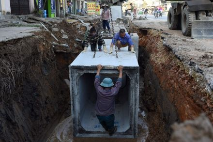 Workers install underground drainage on a street in Hanoi.