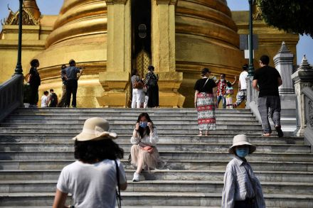 Mask-wearing tourists at the Grand Palace in Bangkok.