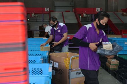 Staff of e-commerce firm Qoo10 work in the company's sorting facility.